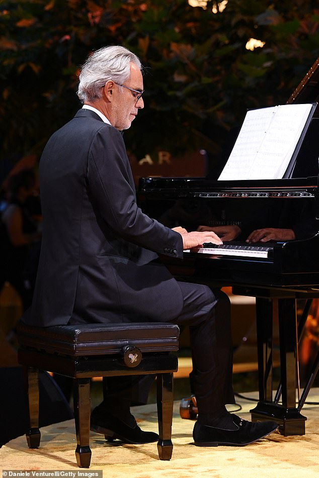 Taking a seat: Although the father-son duo performed alongside each other during the dinner, Andrea was also seen to take a back-seat role at one point