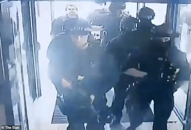 Armed officers storm into the Holiday Inn Express, in Stratford, east London, after a man was spotted with a handgun