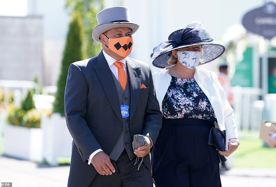 Coordinated chic! One gentlemen opted for an orange facemask with matching tie as part of his three-piece suit while his partner teamed up a navy outfit with a silky face mask