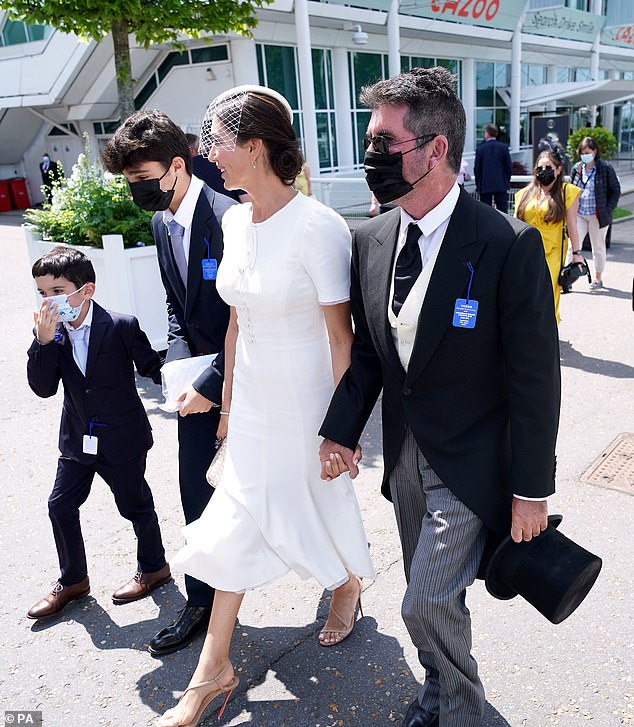 Day at the races: Simon Cowell cut a dapper figure at the Epsom Derby with partner Lauren Silverman, 43, their son Eric, seven, and her son Adam, 15, onSaturday