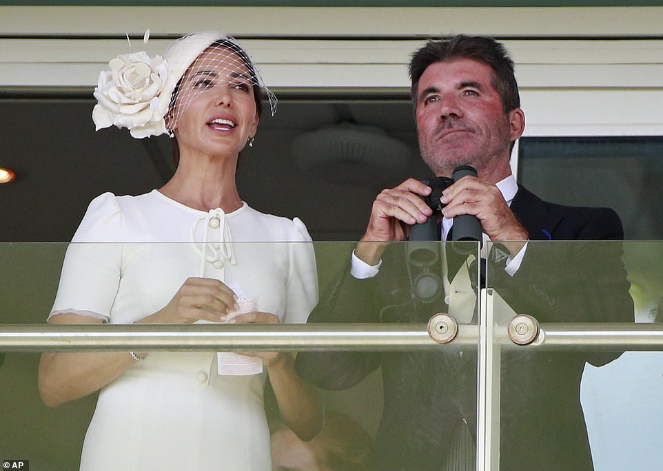 Keeping a lookout: Simon sported a pair of binoculars as he and Lauren watched the festivities in Surrey today