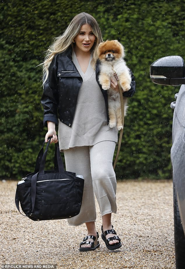 Stylish arrival:Arriving with her beloved pet dog tucked under her arm, Georgia looked chic in a material co-ord