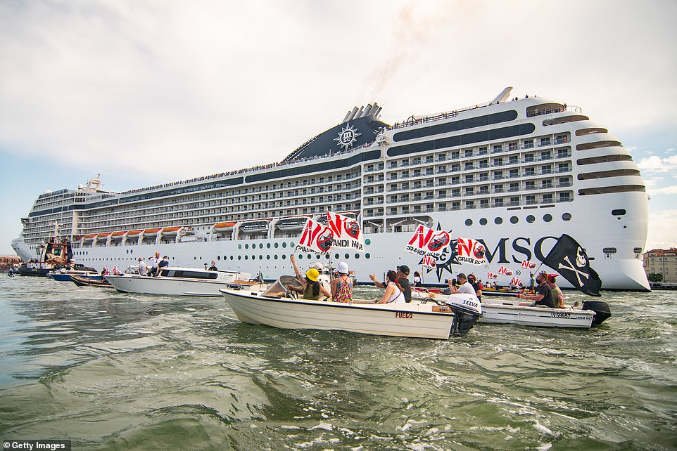 Angry locals say the enormous vessels - weighing over 90,000 tons and carrying thousands of passengers each - pose environmental and safety risks to the canal and the city. Pictured:Protesters take action during the passage of the Cruise Ship MSC Orchestra on June 05, 2021 in Venice