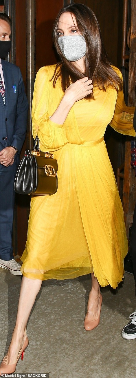 Looking on the bright side: Angelina swapped her signature black wardrobe for a yellow party frock
