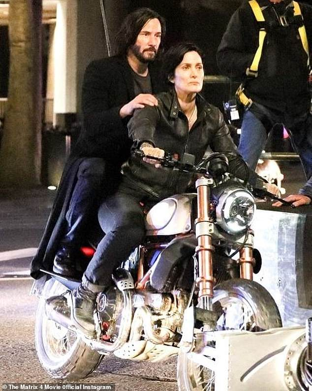 Back in the saddle: Lead actors Keanu Reeves and Carrie-Ann Moss join franchise favoritesPinkett-Smith (Niobe), Daniel Bernhardt (Agent Johnson) and Lambert Wilson (The Merovingian); the leading man and lady are pictured in a scene from The Matrix 4