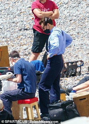 In blue: He donned square sunglasses and showcased a 50s-style quiff as he chatted to crew