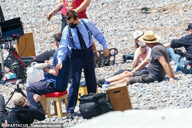 Feelin' hot! Harry removed the hat and his blazer in between takes to keep cool