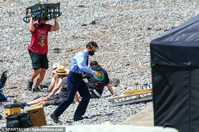 Dressed up: Unlike his last foray on the sand, which saw him strip down to his underwear and film a sequence taking a dip in the freezing waters, Harry was fully-clothed in his officer uniform