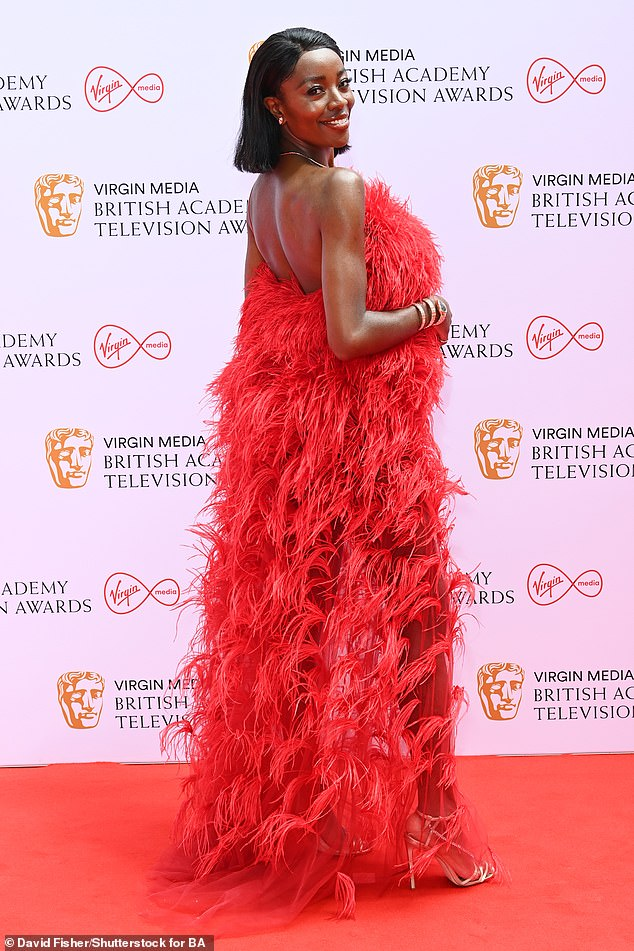 Gorgeous: AJ took to the carpet with confidence as she worked her angles for the camera in the feathered gown, which featured a sultry backless detail