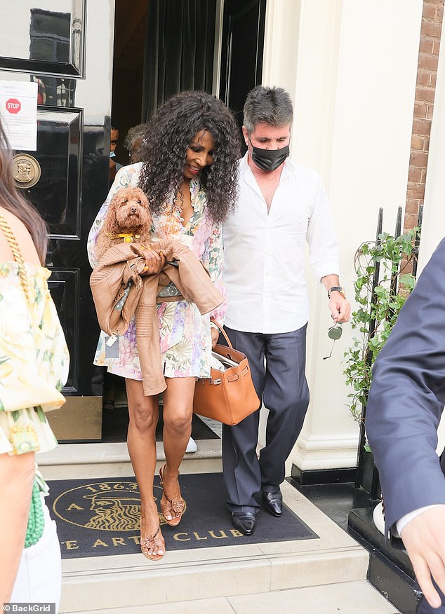 Pins on show: Sinitta slipped into a thigh-skimming dress and carried her beloved pet dog under her right arm