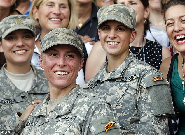Army 1st Lt. Shaye Haver, center, and Capt. Kristen Griest, right, pose for photos with other female West Point alumni after an Army Ranger school graduation ceremony at Fort Benning. Haver and Griest became the first female graduates of the Army's rigorous Ranger School. The Supreme Court is now being asked to consider whether the draft should apply to women as well as men