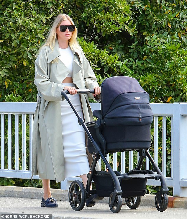 Model: The former Victoria's Secret Angel, 32, added a green trench coat and stepped out in a pair of black Chanel loafers. She sported angular sunglasses and wore her blonde hair loose