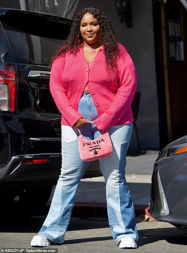Stylish!The singer, 33, went braless in a plunging pink cardigan, which she left slightly unbuttoned, and teamed with high-waisted mom jeans