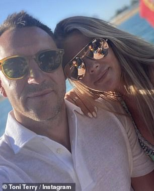 Cute: John wore a white polo for the selfie while Toni was clad in her bikini