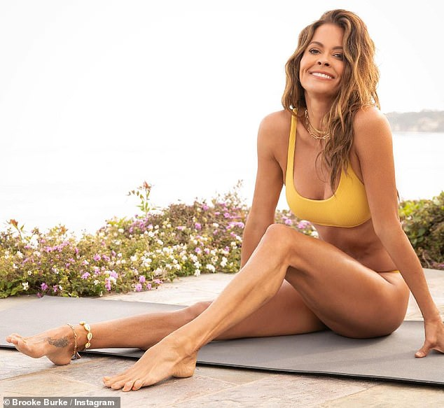 Flawless:The Dancing With The Stars vet, 49, had a very flat tummy with sculpted arms and legs as she made the most of the yellow two piece by San Lorenzo