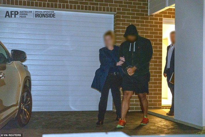 A suspected gangster is detained by Australian police during their massive raid on the criminal underworld