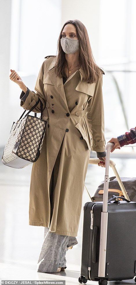 Traveling in style: The Maleficent star was seen wearing a Christian Dior trench coat as she lead her large family out of the airport, also carrying a Celine tote bag and Louis Vuitton luggage