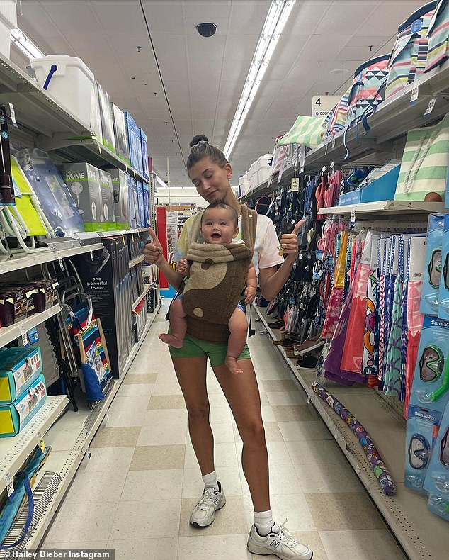 Maternal: Kelia snapped pictures of Hailey in a convenient store with her baby son strapped to her chest
