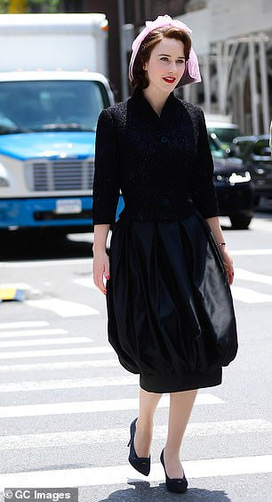 Style: She completed the chic ensemble with suede navy heels and wore a retro pink hair net over her brunette tresses
