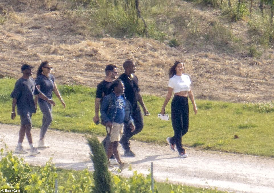 Part of the family: Irina can be seen smiling as she takes a stroll with Kanye and his team while on a romantic trip to France