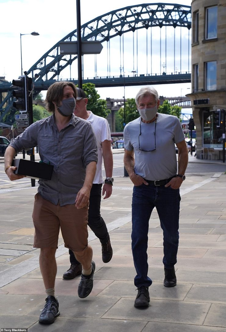 Walk and talk: The star wore a face mask as he strolled down the street in the city