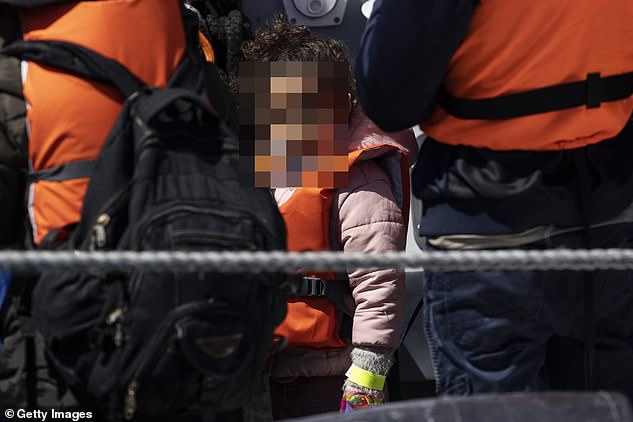 Lucy Moreton, of the Immigration Services Union, said that staff were reporting between five and 10 arrivals every day were testing positive upon arrival (pictured: Border Force officials guide newly arrived migrants)
