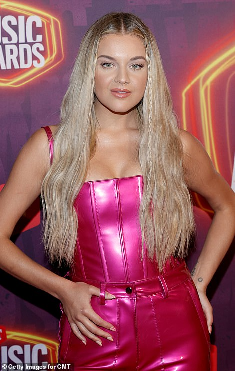 Blonde bombshell: She wore her lengthy blonde hair in waves with two braids in the front to frame her face