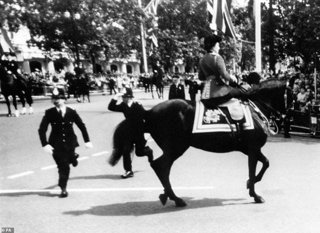 1981 — A FRIGHTENING CEREMONY:Queen Elizabeth II calms her horse Burmese while policeman spring to action after shots were heard as she rode down the Mall.The 1981 ceremony saw Marcus Sarjeant,of Folkestone, Kent, fire six blank cartridges at the Queen as she turned down Horseguards Parade for the start of the Trooping the Colour ceremony. Sarjeant was sentenced to five years' imprisonmentunder the Treason Act.