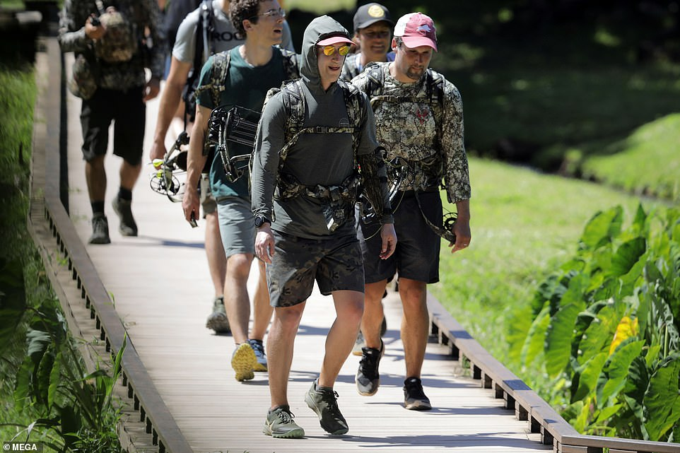 Let's go boys! Zuckerberg and his friends setting off on their hike on Wednesday after he told staff he was going to keep working from home
