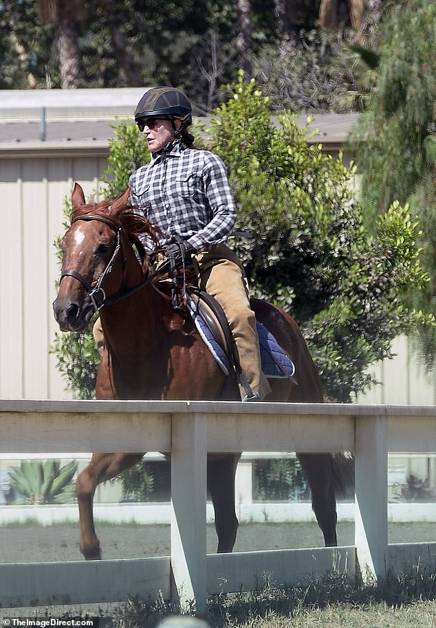 Focused: The 58-year-old reality TV star donned a plaid shirt with riding pants and a helmet during her riding session
