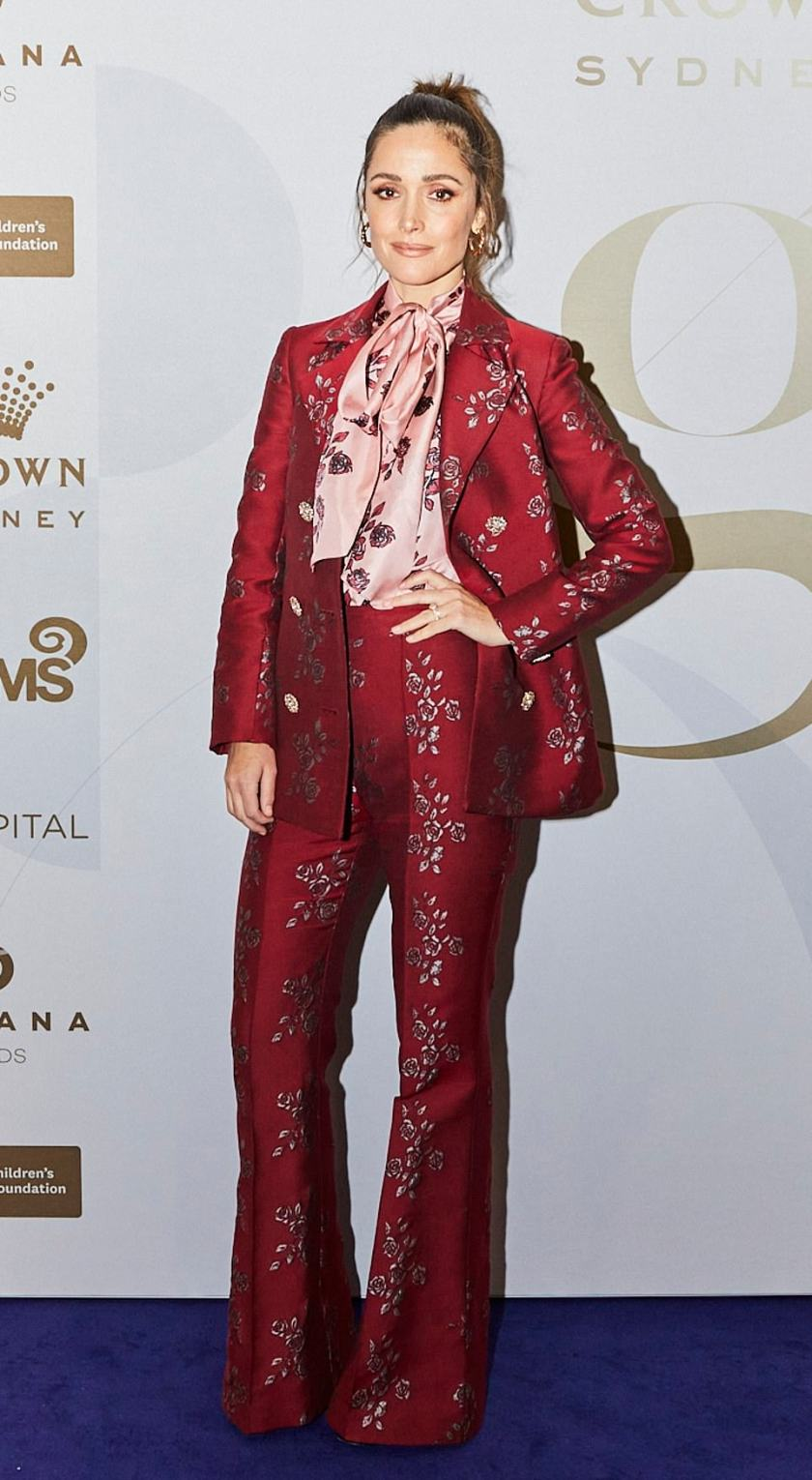 Androgynous chic: Rose Byrne turned heads in a red pantsuit featuring gold floral detailing and a matching pink cravat