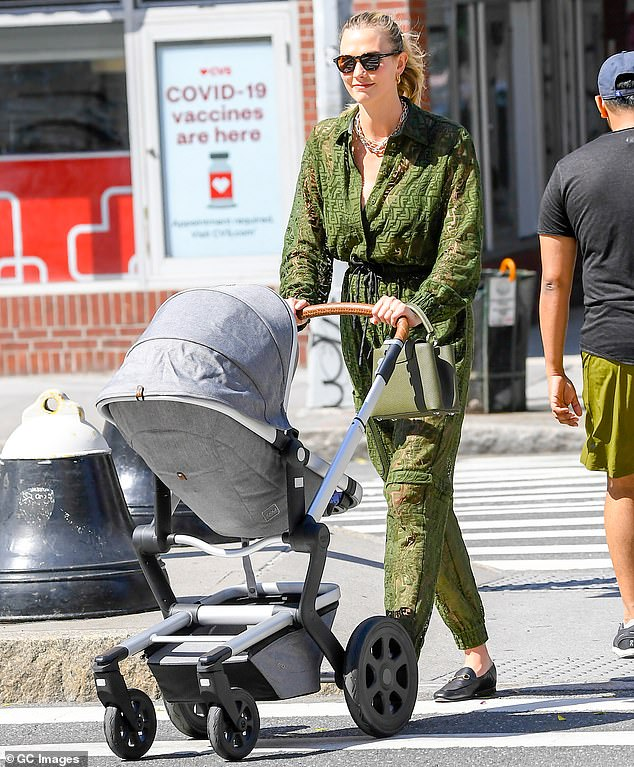 Happy mom: Karlie Kloss proved she was still fashionable as ever while spotted taking her newborn son Levi Joseph for a walk in New York City on Thursday afternoon