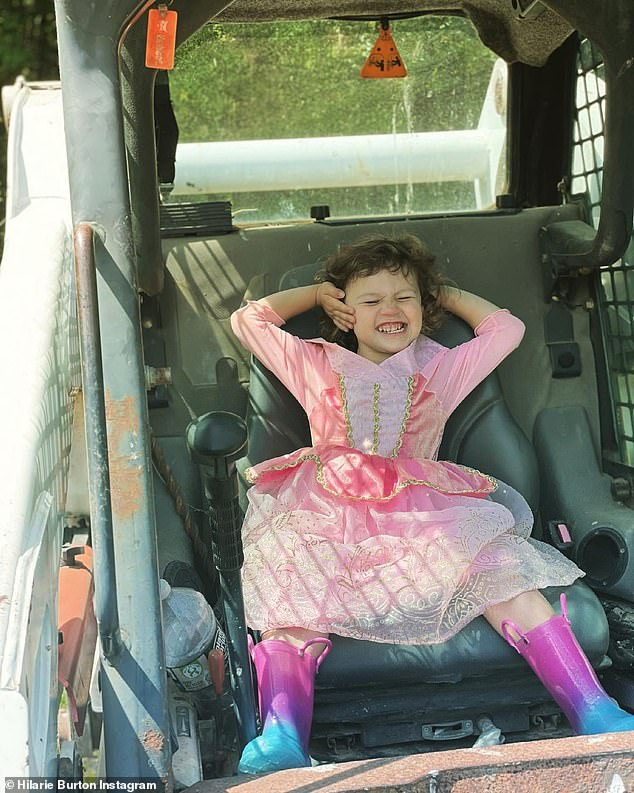 All smiles:George was all smiles in an adorable pink princess dress with pink rubber boots, while sitting on the Bobcat