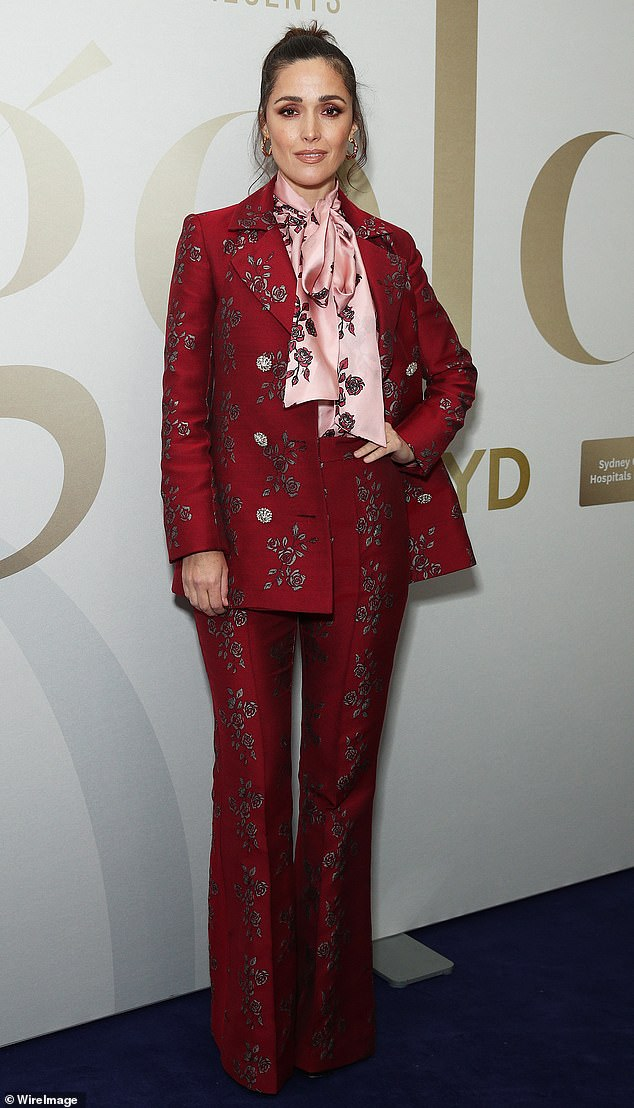 Raspberry beret!  Rose Byrne channeled Prince in a stunning red floral suit and matching bow tie blouse valued at $ 2,385 at the Starry Dinner at Sydney Airport on Thursday night