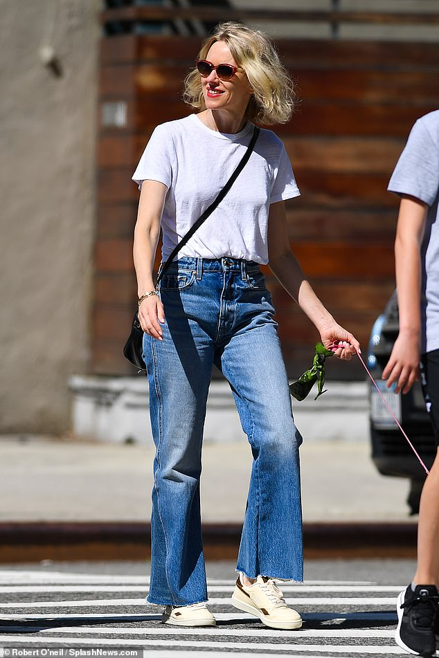 She shines !  Young Naomi Watts, 52, beamed that she took her beloved dog Izzy for a walk around New York City in a pair of flared jeans on Thursday