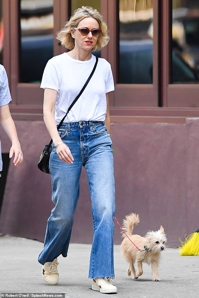 Casual chic: The British-born star kept her casual look, wearing a loose white t-shirt that she tucked into a pair of flared jeans