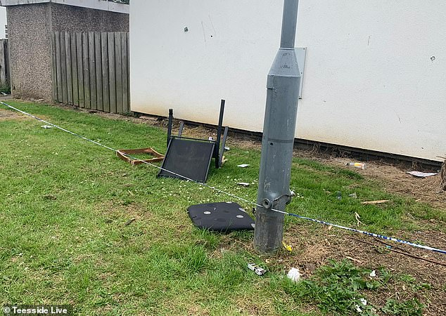 An upside down chair, pizza box, table and rubbish can be seen outside the property