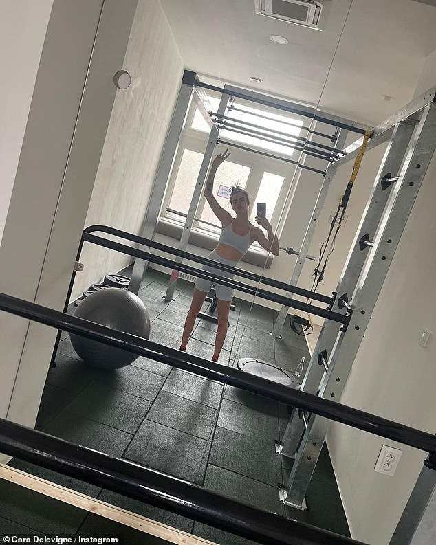 Exercising: Another image, taken during a session in the gym, showed Cara wearing grey exercise gear and holding her hand up to make a peace sign in the mirror