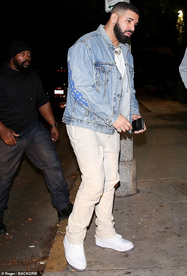 Stylish:Drake wore a plain white T-shirt beneath his light wash jacket and accessorised with a colourful beaded necklace