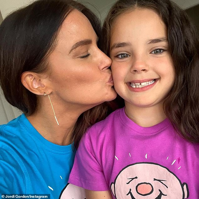 Aww: In the photos, the mother and daughter huddled together and shared a soft kiss on the cheek