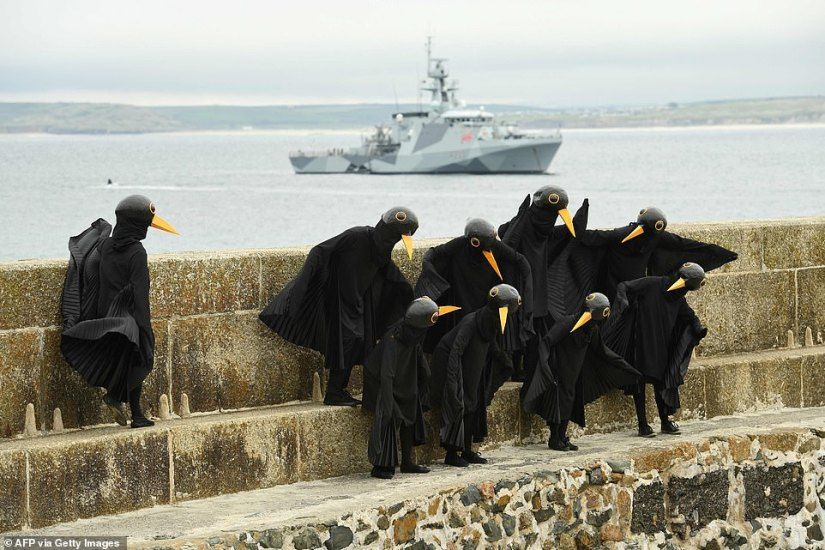 Protesters dressed as blackbirds and put on a display in St Ives as they demonstrated against climate change inaction
