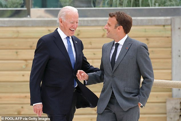 President Joe Biden (left) put his hand on the back of French PresidentEmmanuel Macron (right) as world leaders greeted each other at the start of the G7 Friday in Cornwall