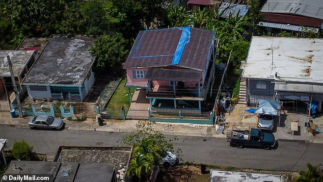 Blue tarps are seen atop Clotilde Rivera's, home which appears to still sustain damages since the passing of Hurricane Maria and Hurricane Irma in 2017