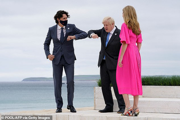 As Trudeau approached he put on a face mask before bumping elbows with Boris and turning his attention to Carrie to say: 'It's lovely to meet you Carrie'