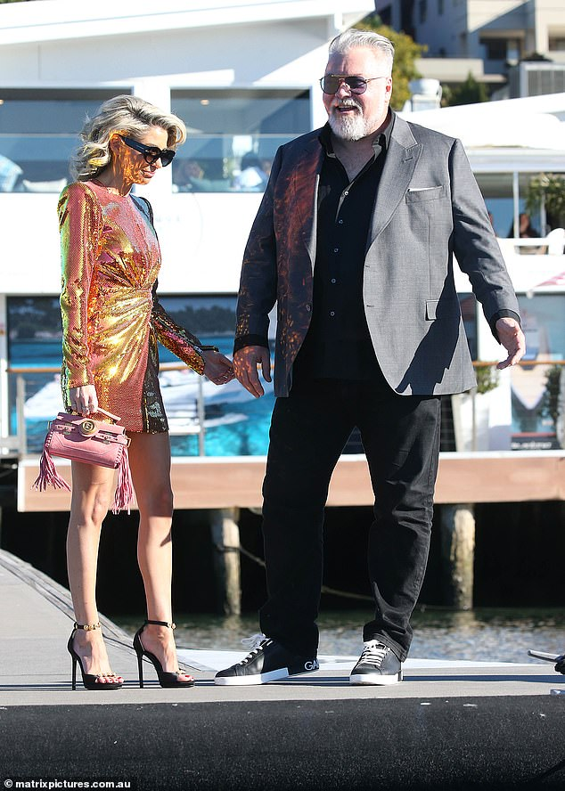 Party time: Arriving fashionably late! Kyle Sandilands (right) looked loved up with his glamorous girlfriend Tegan Kynaston (left) on Saturday as they waited for a boat to take him to his 50th birthday cruise on board a superyacht on Sydney Harbour