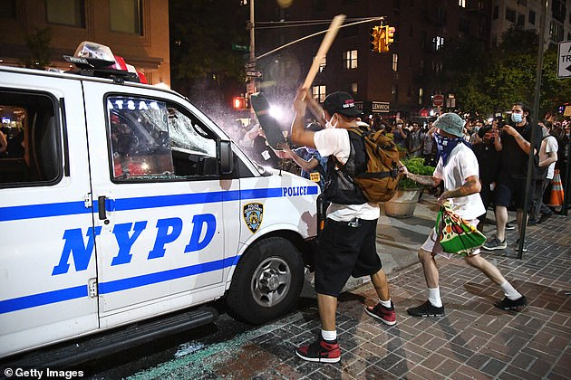 Protesters vandalize an NYPD van near Union Square in Manhattan on May 30, 2020