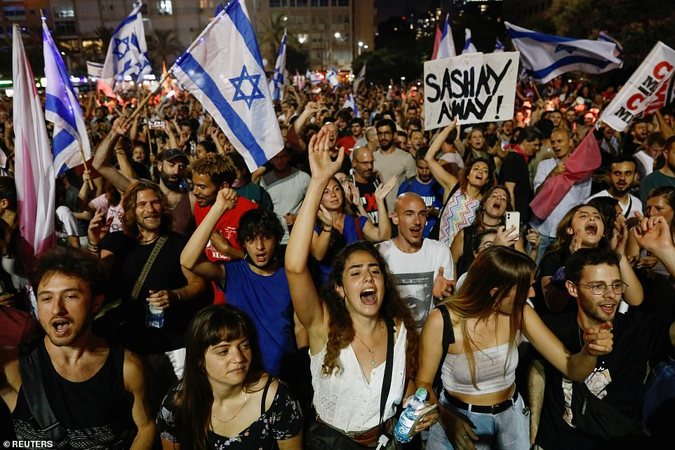 People cheer as they celebrate the confidence vote which has meant a new coalition has formed a government. A woman held a sign which seemingly told Netanyahu to 'sashay away'