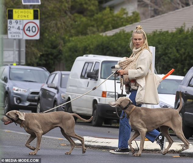 Juggling act! Elyse Knowles, 28, was every inch the multitasking mama as she carried her newborn Sunny in a sling while grabbing a coffee and taking her dogs for a walk in Byron Bay on Thursday