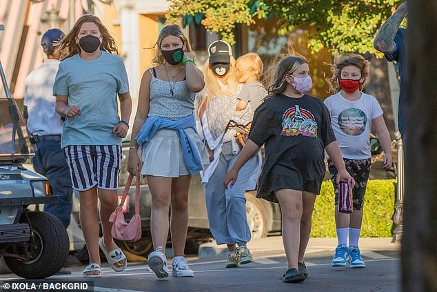 Keeping it safe: The family kept their face covered with masks on the sunny day