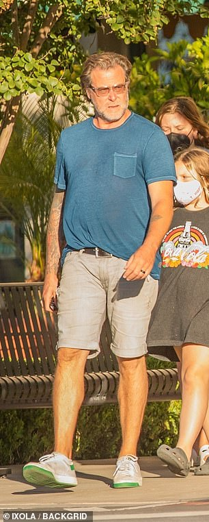 Sunny day:McDermott wore an ocean blue T-shirt ticked into a pair of light blue shorts with white trainers